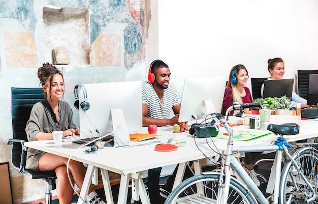 Gente di affari dei pantaloni a vita bassa che si diverte a lavorare sul computer all'ufficio dello spazio di coworking - il web moderno avvia il concetto di felice atteggiamento produttivo