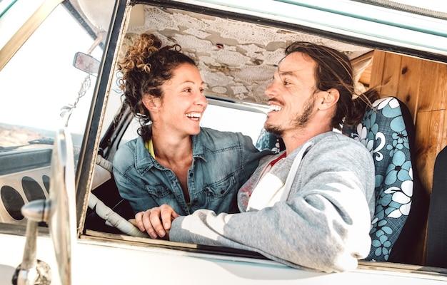 Coppia hipster che guida in viaggio su un minivan d'epoca - concetto di stile di vita di viaggio con persone indie che si divertono in momenti di relax durante un viaggio di avventura in minivan - filtro caldo e luminoso