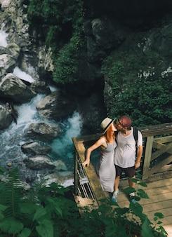 Coppia hipster escursionismo sullo sfondo di un fiume di montagna slovenia tolmin
