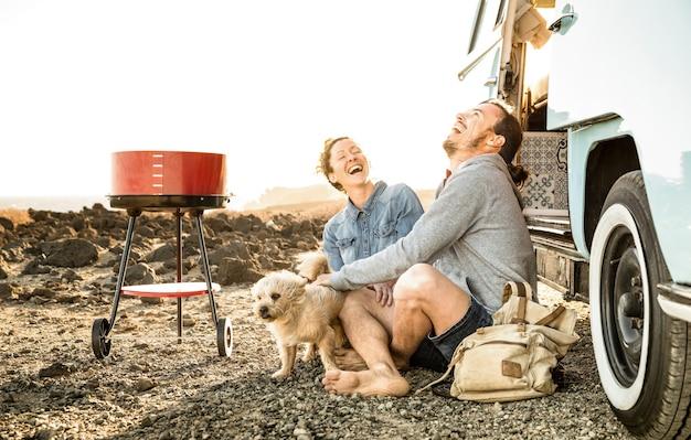 Coppia hipster con cane carino che viaggiano insieme sul trasporto di mini van d'epoca - concetto di stile di vita di viaggio con persone indie in viaggio di avventura in minivan divertendosi nel momento del barbecue - filtro retrò caldo