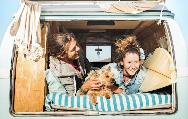Coppia di hipster con cane carino che viaggiano insieme sul trasporto di mini van vintage