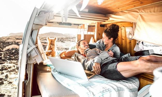 Coppia hipster con cane che viaggiano insieme sul trasporto di mini van retrò