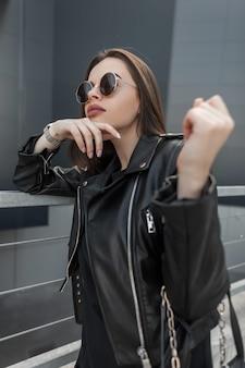 Hipster bella ragazza alla moda con occhiali da sole rotondi vintage in giacca di pelle nera alla moda con elegante borsa alla moda passeggiate in città