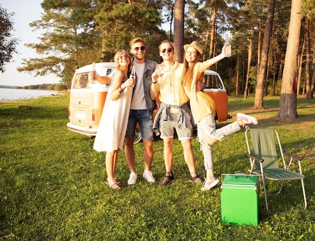 Amici hipster in camper al festival in una giornata d'estate.