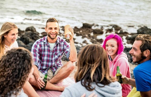 Amici hipster che si divertono insieme alla festa in campeggio sulla spiaggia
