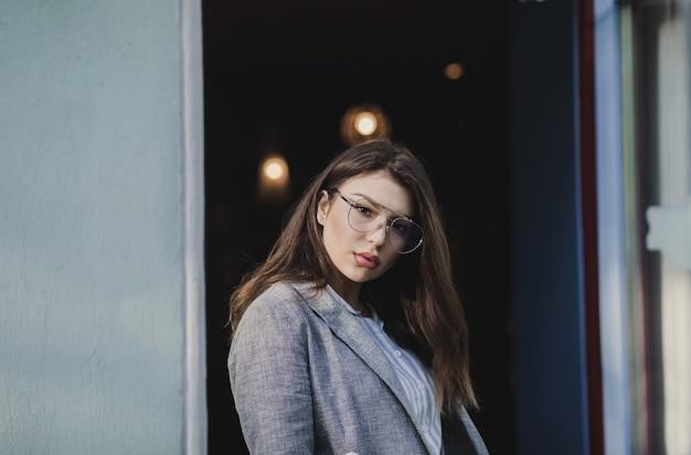 Ragazza hipster in giacca in posa sulla strada cittadina. giovane donna che indossa un look elegante.