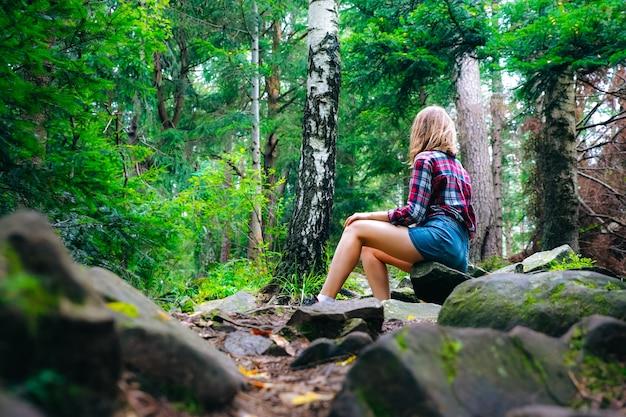 Ragazza hipster in montagna. donna alla moda in camicia a scacchi che si siede sulle pietre nella foresta. concetto di voglia di viaggiare. escursioni e viaggi in estate. legno misterioso. natura meravigliosa.