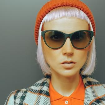 Ragazza hipster con cappello rosso e cappotto a scacchi in stile moda
