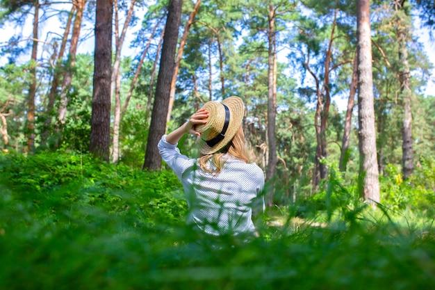 Ragazza hipster in cappello di paglia che si siede nella foresta. concetto di voglia di viaggiare. idee in viaggio. bella donna nella natura nell'erba. vibrazioni estive.
