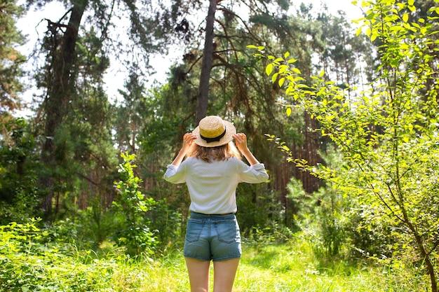 Ragazza hipster in cappello di paglia in piedi nella foresta. concetto di voglia di viaggiare. idee in viaggio. bella donna nella natura. vibrazioni estive.