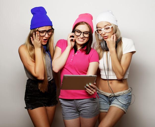 Amici di ragazze hipster con tavoletta digitale sopra bianco