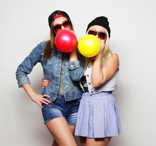 Ragazze dei pantaloni a vita bassa che sorridono e che tengono i palloni colorati