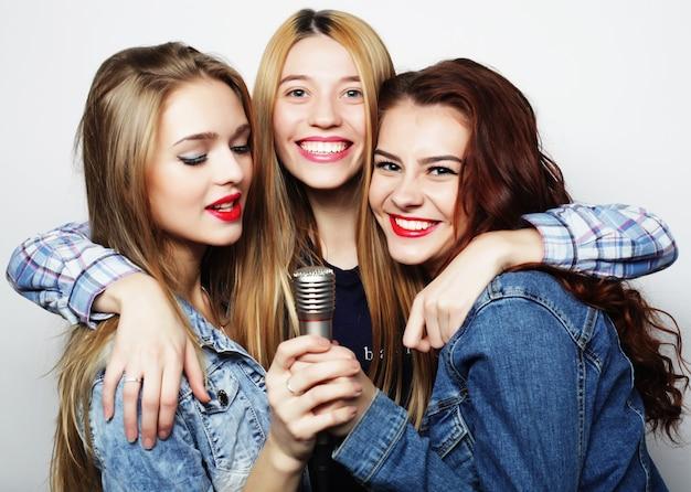 Ragazze hipster con un microfono che cantano e si divertono