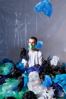 Ragazzo hipster seduto, legato alla bocca con un sacchetto di plastica, circondato da sacchetti di plastica, che guarda l'obbiettivo.