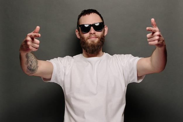Bel modello maschile hipster con barba che indossa una maglietta bianca vuota e un berretto da baseball con spazio per il tuo logo o design in stile urbano casual