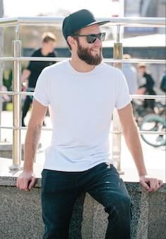 Modello maschio bello hipster con barba che indossa t-shirt bianca vuota con spazio per il tuo logo o design in stile urbano casual
