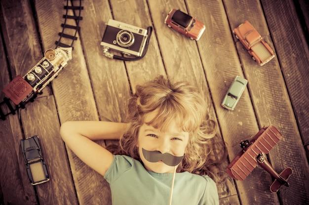 Bambino hipster con giocattoli in legno vintage a casa. girl power e concetto di femminismo