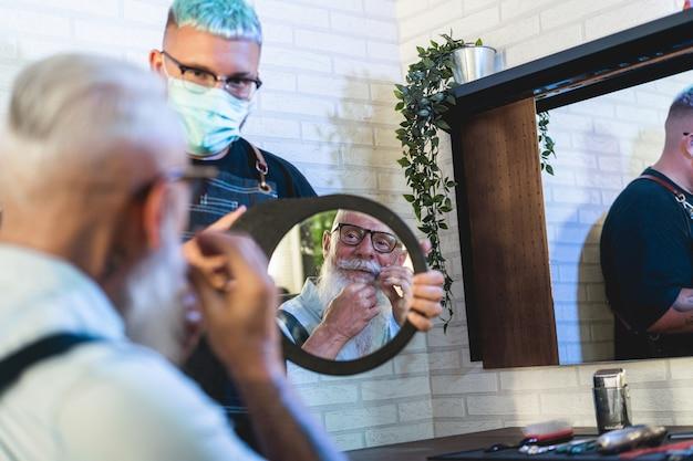 Uomo di hipster che controlla i capelli e il taglio di barba all'interno del negozio di barbiere