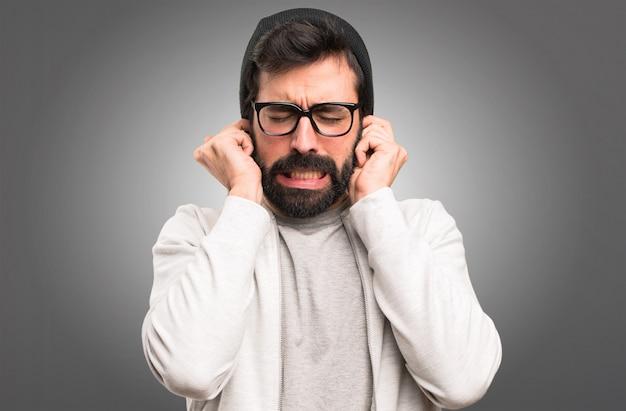 Uomo dei pantaloni a vita bassa che copre le sue orecchie su fondo grigio