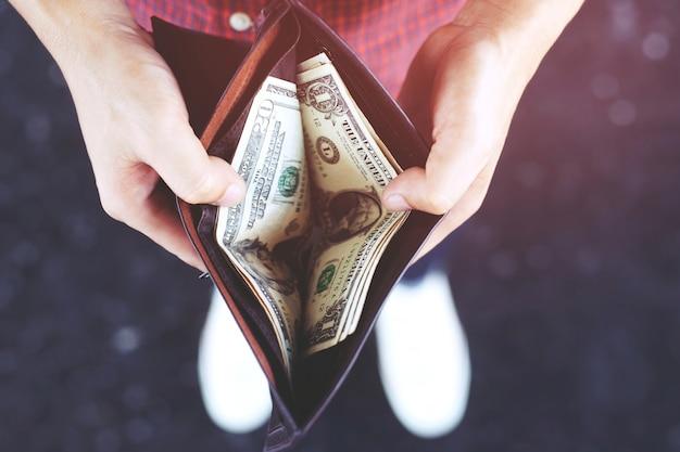 Mani dell'uomo hipster che tengono portafoglio con carte di credito e pila di soldi.