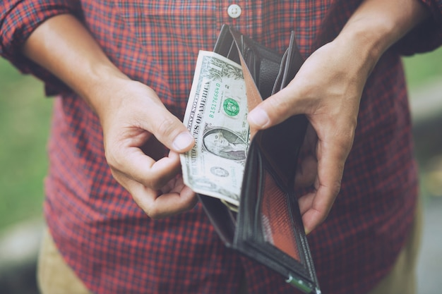 Mani dell'uomo hipster che tengono portafoglio con carte di credito e pila di soldi