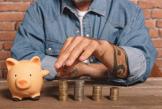 L'uomo dei pantaloni a vita bassa impila le monete con un porcellino salvadanaio sul tavolo per risparmiare denaro e concetto finanziario.