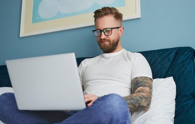 Uomo hipster che usa il laptop a casa