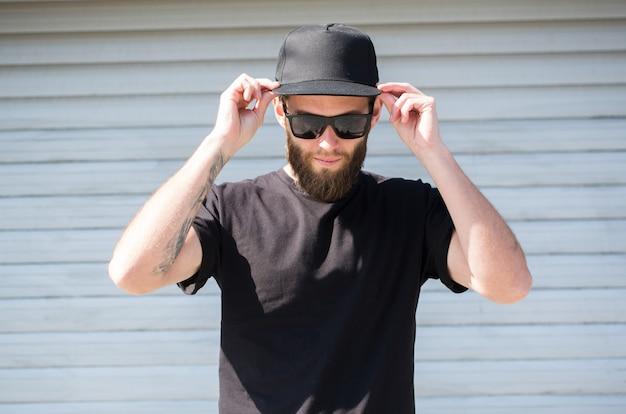 Uomo hipster che indossa una maglietta nera e un cappello nero con spazio per il logo