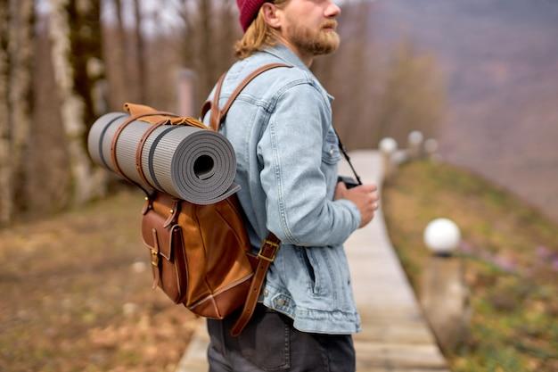 Uomo hipster con zaino che esplora la natura in primavera, camminando da solo all'aperto