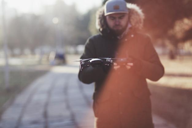 Uomo hipster con drone volante nel parco