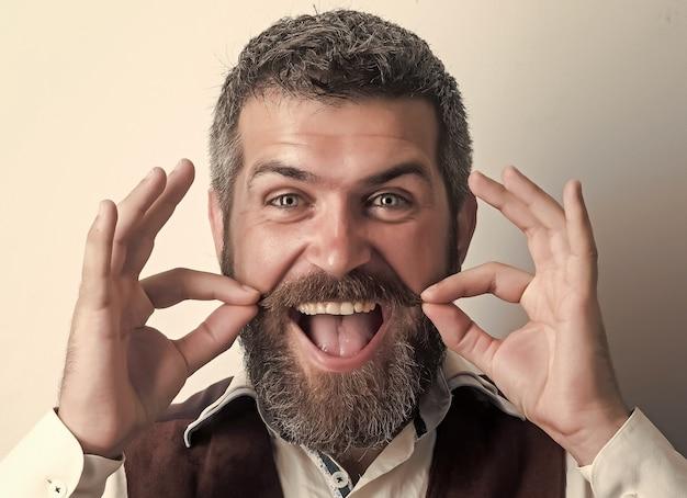 Uomo hipster con barba lunga e baffi sulla faccia felice. modello maschile di moda. ragazzo o uomo d'affari barbuto. moda e bellezza del barbiere. negozio di barbiere, concetto di negozio di barbiere.
