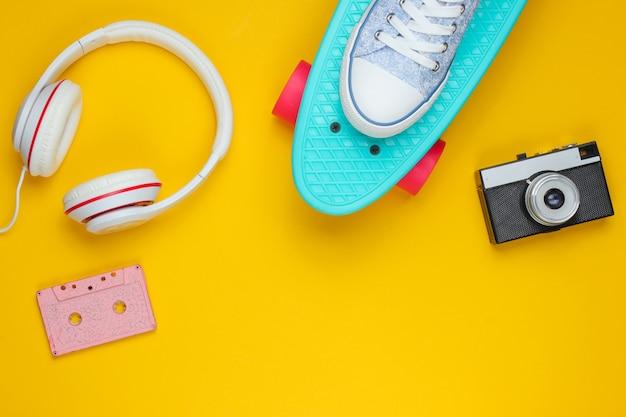 Vestito hipster. skateboard, cuffie, audiocassette, scarpe da ginnastica, fotocamera retrò su sfondo giallo. minimalismo della moda creativa. minimo divertimento estivo. pop art. anni 80. copia spazio. vista dall'alto