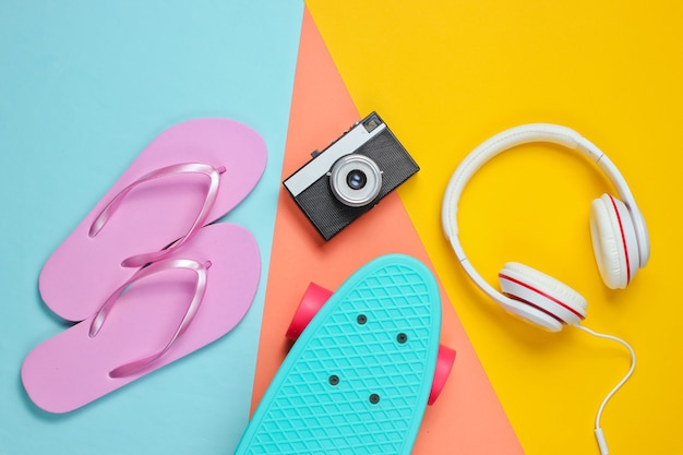 Vestito hipster. skateboard con cuffie, flip flop, fotocamera retrò su sfondo colorato. minimalismo della moda creativa. stile retrò anni '80 alla moda. minimo divertimento estivo.