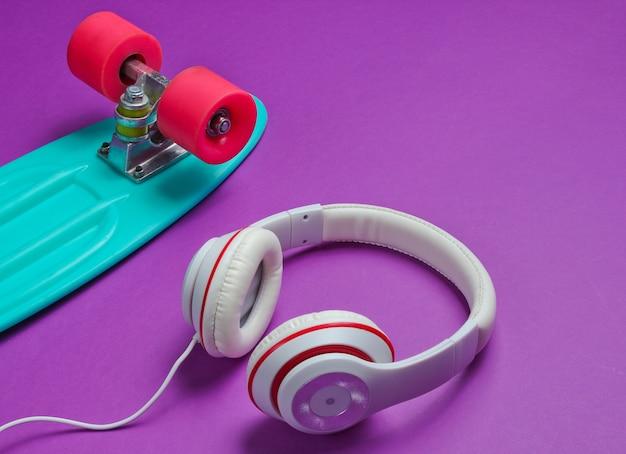 Vestito hipster. skateboard con le cuffie su sfondo viola. minimalismo della moda creativa. vecchio stile alla moda alla moda. minimo divertimento estivo. concetto di musica