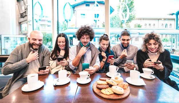 Gente di hipster che esulta a notizie positive su smart phone mobile al bar
