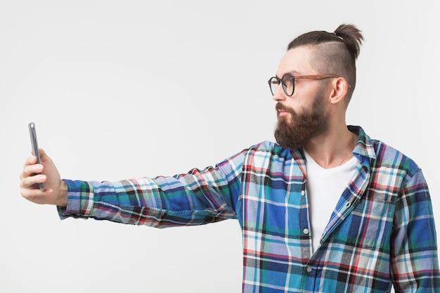 Hipster, concetto di persone. giovane hipster con la barba in bicchieri prendendo selfie