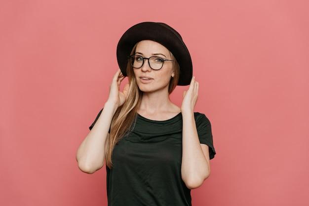 Giovane donna rossa hipster in occhiali, t-shirt casual verde scuro e cappello con tesa