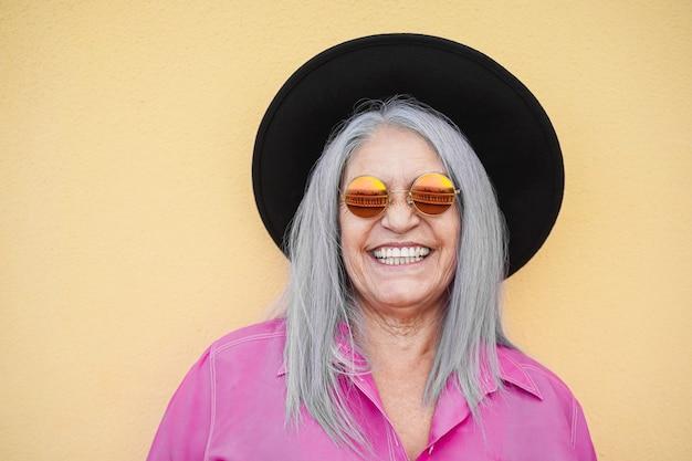 Donna senior dei pantaloni a vita bassa che sorride e che posa