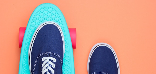 Scarpe da ginnastica hipster su vista dall'alto di skateboard su sfondo corallo. il minimalismo del concetto di moda