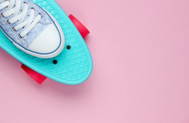 Sneakers hipster su vista dall'alto di skateboard su sfondo rosa. il minimalismo del concetto di moda