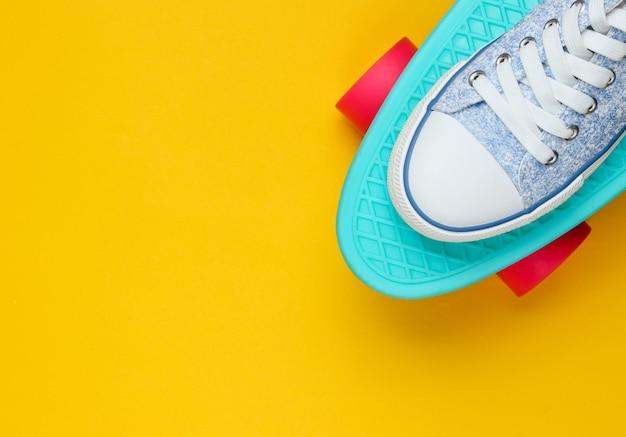Sneakers hipster su vista dall'alto di skateboard su sfondo giallo. il minimalismo del concetto di moda. copia spazio