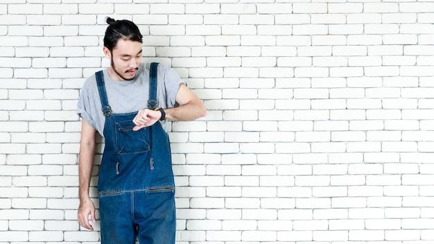 Uomo asiatico in stile hipster che indossa un grembiule magro in piedi su un muro di mattoni bianchi e guarda a guardare