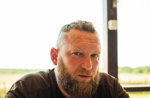 Uomo barbuto stile hipster. l'uomo attraente la bionda con i capelli lunghi dall'aspetto europeo con la barba. uomo in maglietta. ritratto di un uomo.