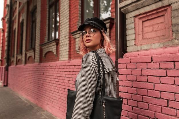 Hipster elegante e graziosa ragazza in abbigliamento casual alla moda con occhiali e un berretto cammina per la strada vicino all'edificio in mattoni del grunge