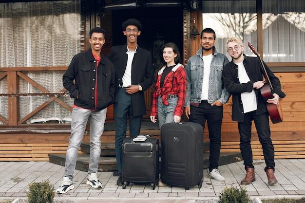 Viaggiatori hipster pronti per un viaggio. uomini indiani e donne che tengono le valigie a casa.