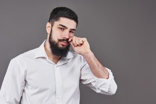 Hipster con faccia seria. sentimento ed emozioni. ragazzo o uomo barbuto su sfondo grigio. moda e bellezza del barbiere. uomo con barba lunga e baffi, copia dello spazio.