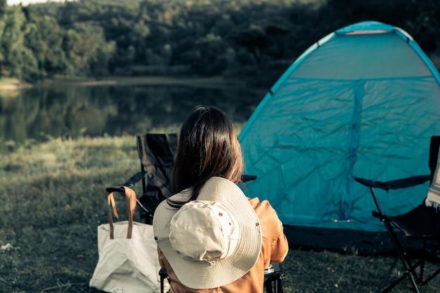 Donna hipster che riposa e si rilassa con il suo campeggio in vacanza e vita lenta.