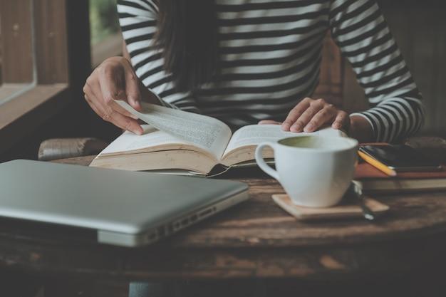 La seduta dell'adolescente della donna dei pantaloni a vita bassa gode di di leggere il libro al caffè