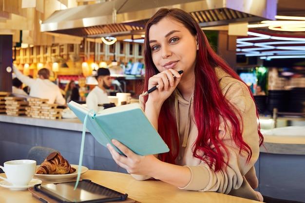 La donna hipster con i capelli tinti di rosso lavora a distanza in un bar con un taccuino tra le mani