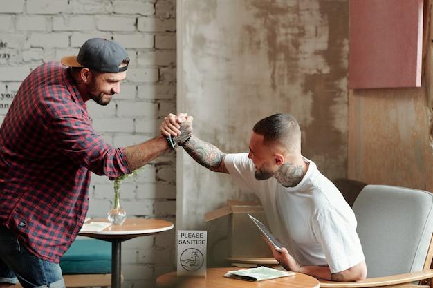 Giovani amici maschi hipster che stringono saldamente la mano mentre si incontrano nella hall dell'hotel durante il periodo del coronavirus
